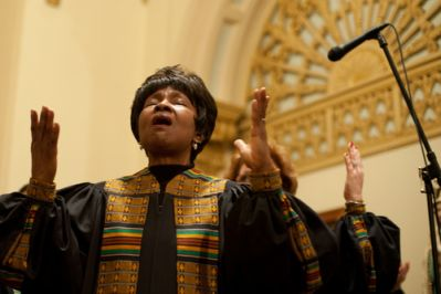 A black woman singing with hands raised at the front of a church