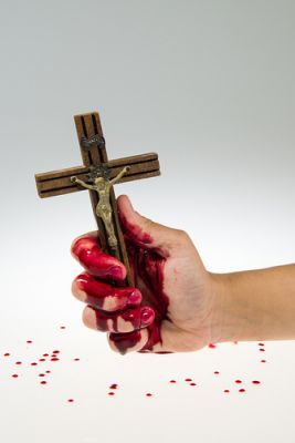 A bloody hand holding a religious figure of a wooden cross