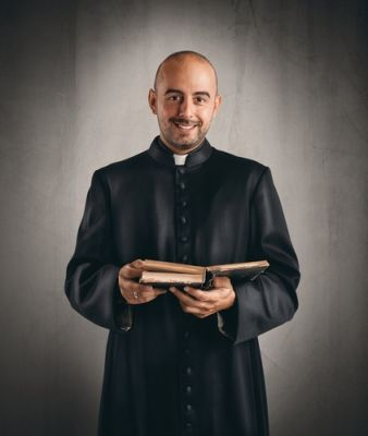 A married Catholic priest holding a Bible
