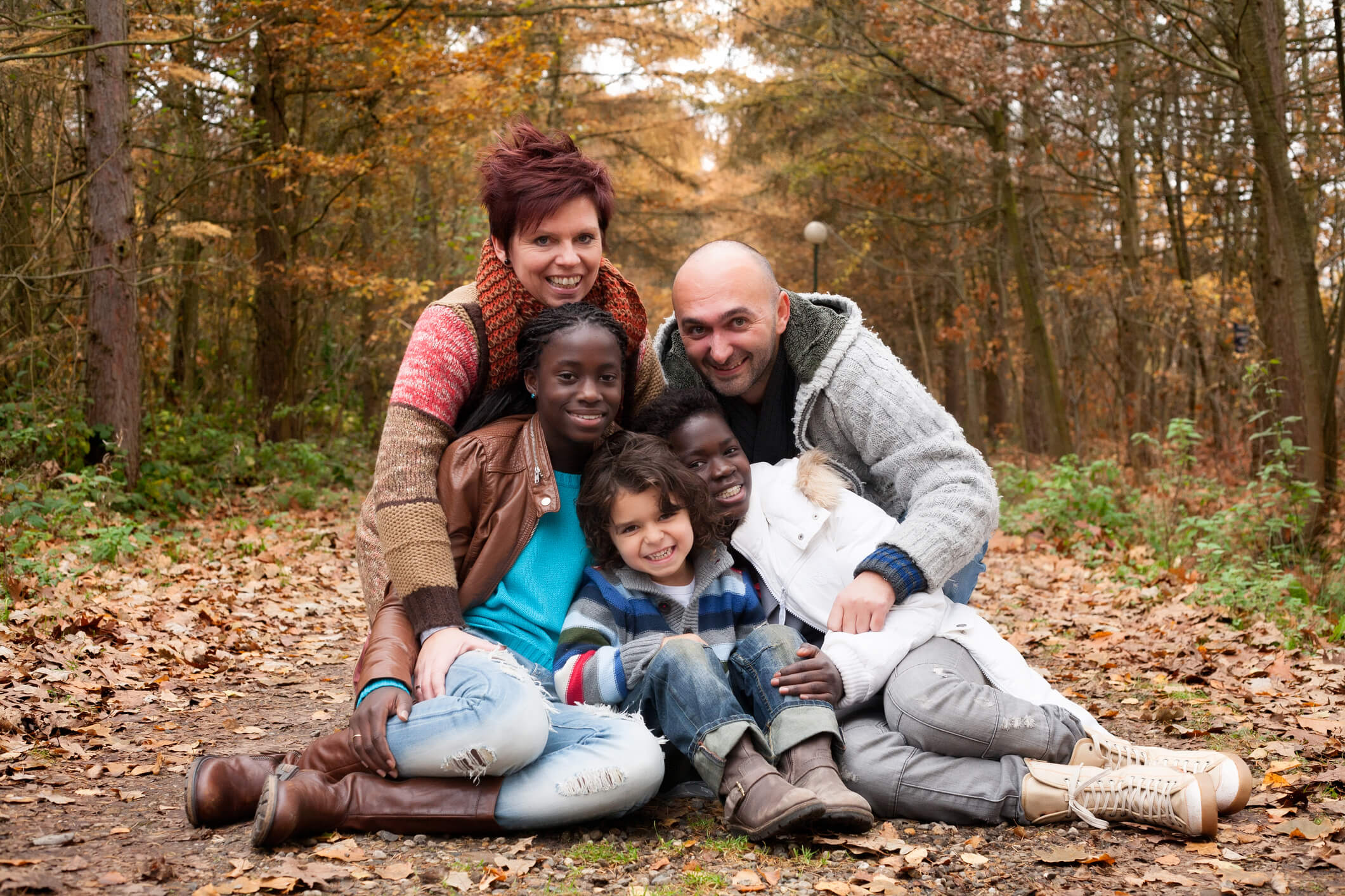 Multicultural family posing in the woods during autumn