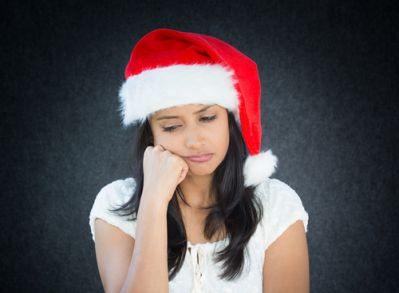 A young woman with grief wearing a Santa hat