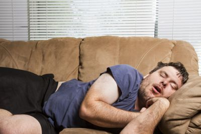 A man exhibiting sloth by sleeping on the couch