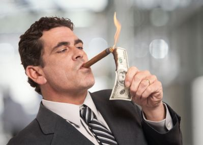 A man showing greed by lighting his cigar with money