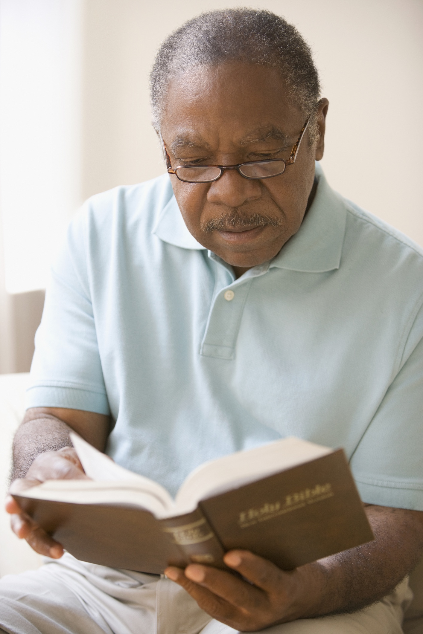 An older man reading a Bible.