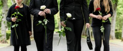 Mourners With Flowers Attending a Humanist Funeral