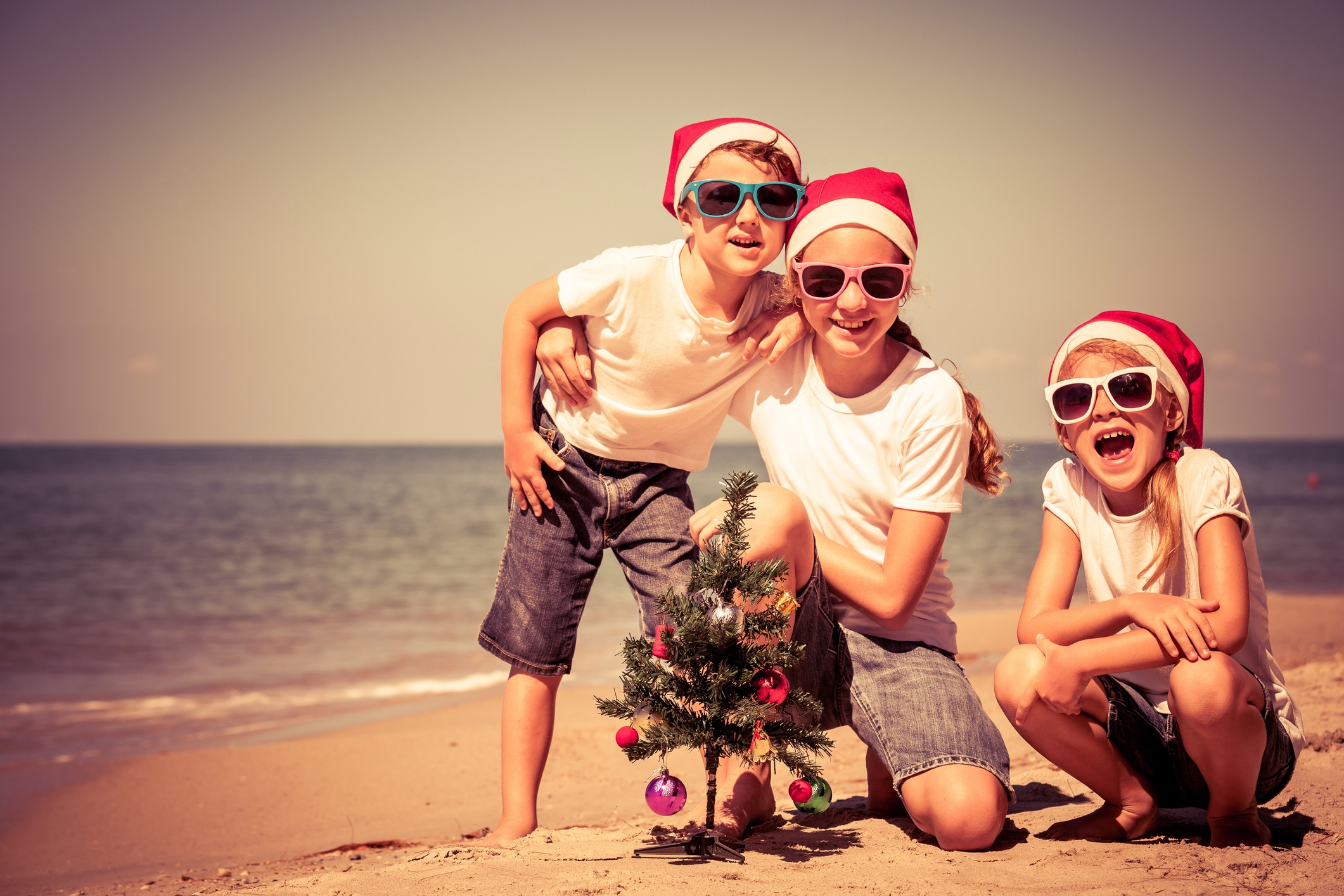 Children wearing Christmas hats on the beach.