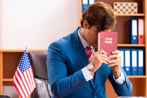 Politician holding Bible at desk