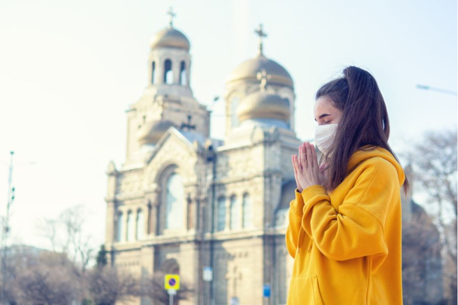 Woman praying with facemask in front of church