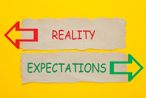 a sign directing expectations and reality