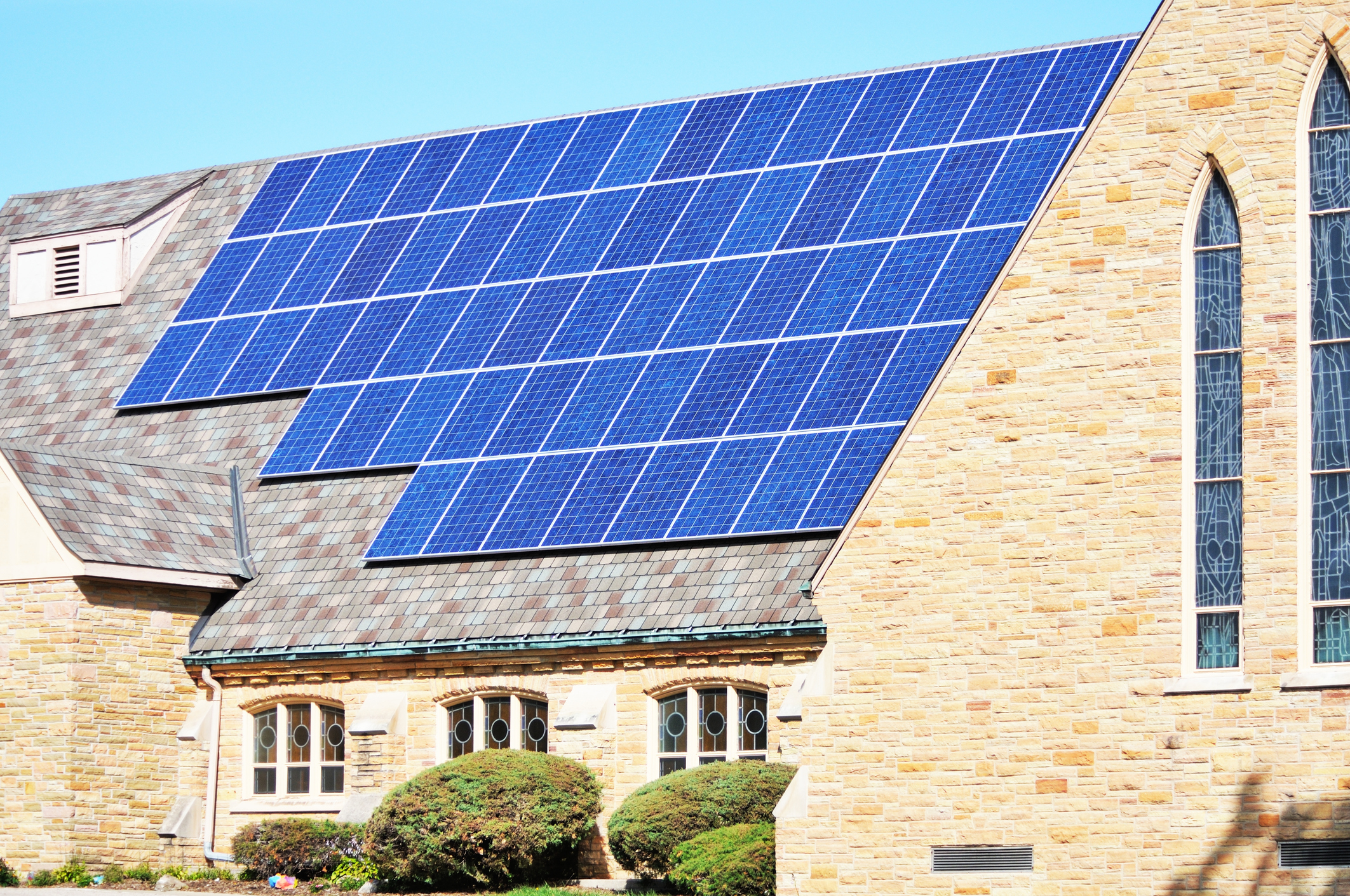 An Episcopal church with solar panels on the roof.