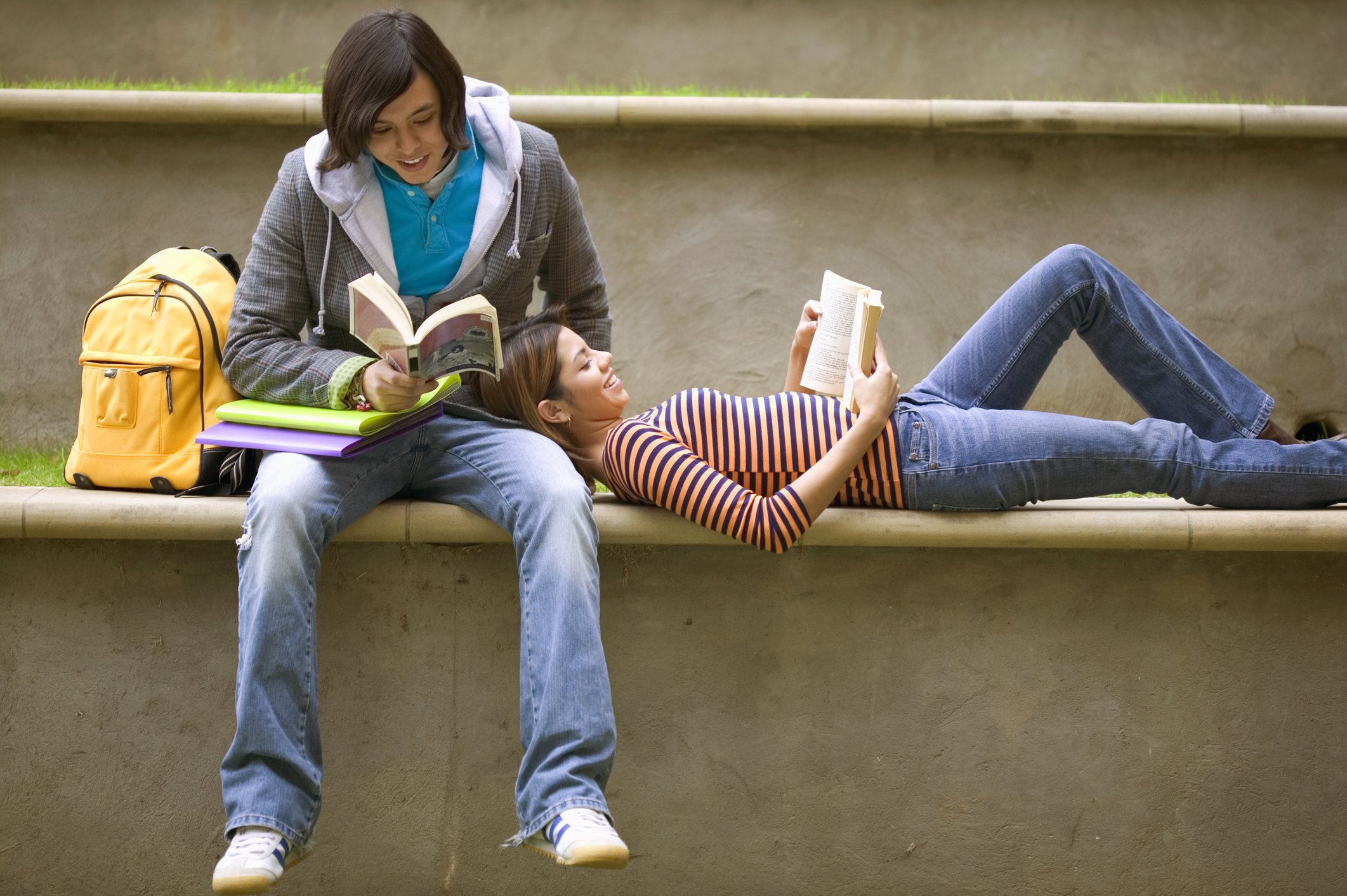 Teenagers relaxing and reading together