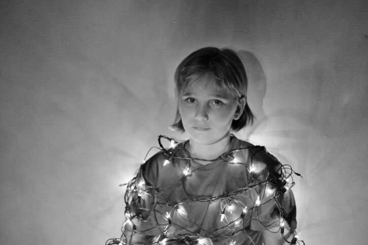 A person wrapped up in Christmas lights